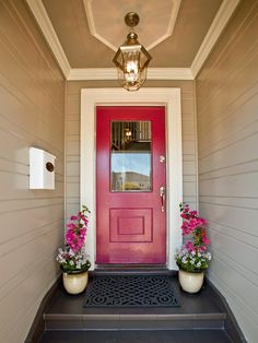 A few coats of fuchsia paint take this formerly ho-hum front door from drab to fab. The cheery pink theme is carried to pots flanking the doorway filled with bouganinvillea and candytuft. The terracotta tile steps and board-and-batten siding also receive a makeover with fresh coats of warm, neutral paint.