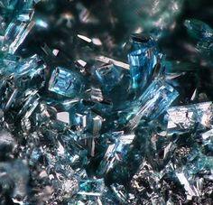 Keyite, Cu++3(Zn,Cu)4Cd2(AsO4)6•2(H2O), Tsumeb Mine, Tsumeb, Otjikoto Region, Namibia. Fov 2 mm. Blue microcrystals on tennantite ore matrix with green cuproadamite xls in a vug and grey crystallized schultenite. Dimensions specimen 4 x 2.8 x 2.2 cm. Uploaded by: Val Collins