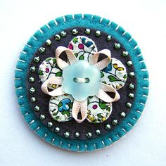 like this pin with the buttons,beads and ribbon accents