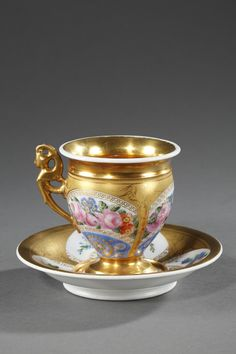 A Sevres porcelain cup decorated with polychromatic flowers and gilded medallions on white background hightened with gold coloured flowery brunches. Saucer with the same golden decoration an