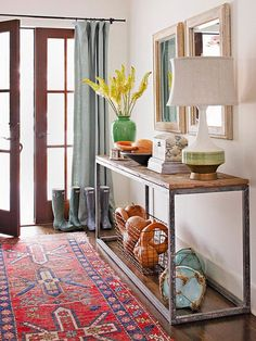 rustic console in entry bhg. I like the decoration below the table. The basket with gourds in it is great. Plus, i love that rug!