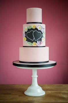 Pink, black, chalkboard and garden flowers in pastels. I love this wedding cake! Photo by @meginzondervan