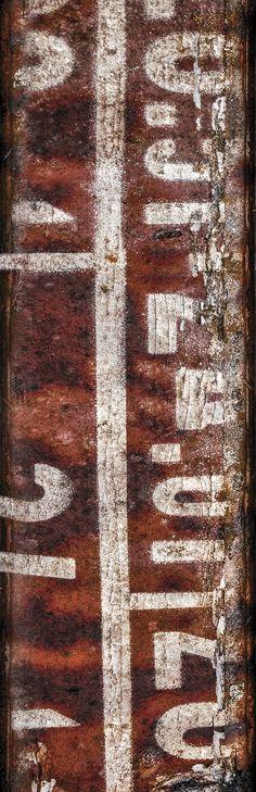 Sign of the Past #02. Bij monumenten zijn aan binnen- en buitenzijde symbolen en iconen zichtbaar. In de vorm van ornamenten, reliëfs en schilderingen. Ook de monumenten zelf hebben een iconische, historische en symbolische waarde. Hoewel men zich dat vaak niet realiseert, geldt dit ook voor industrieël erfgoed.  In het industriële zijn vaak lettertekens en cijfers te zien die een code vormen, die vaak nietszeggend op mensen overkomt. Vorm en achtergrond leveren een aansprekend beeld op.