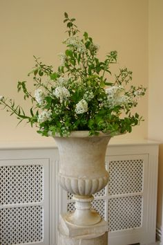 stone urns filled with white lilac, sweet rocket and cow parsley - mid May wild flower wedding - all grown, cut and arranged by @theflowerfarmer at www.commonfarmflowers.com - this venue was the orangery at sherborne castle - lovely place to get married