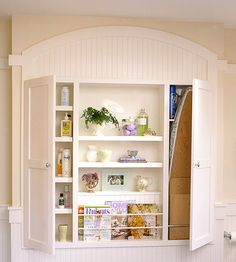 Open and Closed Storage  A built-in unit offers closed storage for supplies and a fold-down ironing board, as well as open shelves and display racks