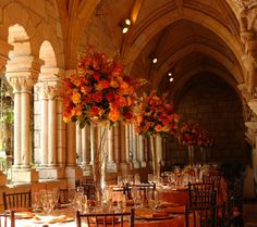 A beautiful centerpiece that is perfect for Fall. Tall Glass Trumpet Vases with submerged curly willy and a top loose arrangement of Orange and High Magic Roses with various greenery