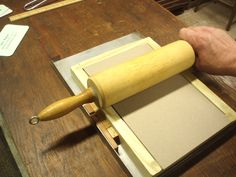 Student Proof Press | Grasp the Roller (with two hands) and draw it across the closed frisket, bearing down hard. The load will be borne by the side rails, but the impression is focused on the type in the stick.   put down the roller, open the frisket and... voila!