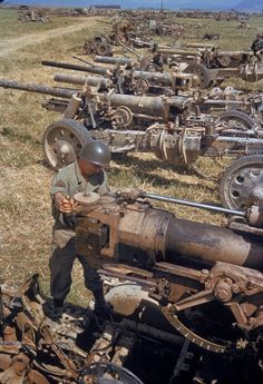 An American soldier looking over German artillery captured or destroyed in the battle of El Guettar, 1943