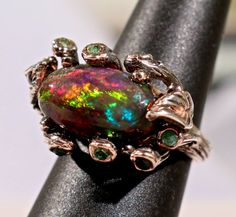Black Beauty!  Sensational Black Opal.  Natural Ethiopian Solid Black opal. Emerald accent gemstones. Sterling Silver leaf design setting.