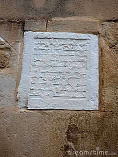 A carved stone plaque featuring arabic writing on a church in Spain which is a relic from the times the moors ruled over Spain.