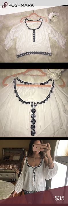 White and Navy Lace Cold Shoulder Shirt Beautiful white shirt with navy lace detail! Never worn because it was a little big on me. It's a medium but can easily fit a large as well! I will steam it before I send it out so it's not so wrinkled. Great condition, no signs of tearing and no stains. Would be beautifully paired with jeans and gold sandals for the spring and summer! :) Tops Blouses