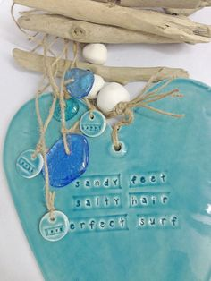 Price:	 Starting at $59.95   Clay heart handmade in Australia. White earthenware clay glazed with a beautiful gloss glaze  Natural twine with clay pebble beads, driftwood and glass make this a beautiful wall hanging.  The message 'salty hair sandy feet perfect surf' has been pressed into the clay. You can personalise this gift by handwriting a message on the back (unglazed side) with a felt pen.  Available in: Medium 160mm h x 140mm w, overall drop length 400mm Large 245mm h x ...