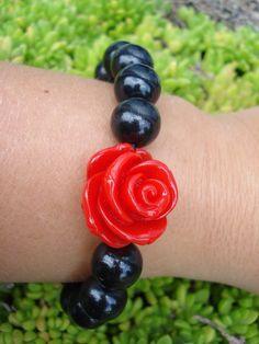 Armband met zwarte kralen en rode roos.