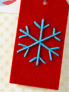 Sketch a snowflake on stiffened felt and stitch the shape with yarn. Then glue it all to a plain tag.