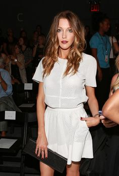 Katie Cassidy gives her white matching separates a pop of color with a red lip shade.