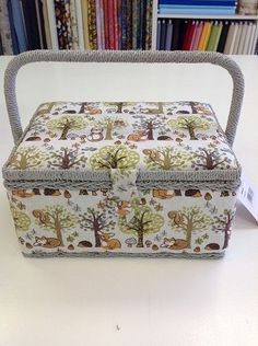 SEWING BOX THIS IS A BEAUTIFUL PADDED WOODLAND SEWING BOX WITH A PLASTIC LIFT OUT TRAY WITH FOUR COMPARTMENTS BEAUTIFUL PADDED LID GREY WICKER HANDLE