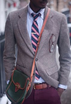 gray/beige blazer, sky-blue seersucker shirt, red/white/navy striped tie, brown leather belt, purple chinos, green bag with tan leather trim and strap.