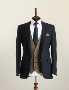 Wedding Suit Hire A mannequin wearing a navy lounge suit jacket with brown check waistcoat and patterned blue tie.A mannequin wearing a navy lounge suit jacket with brown check waistcoat and patterned blue tie. Wedding Suit Hire, Wedding Men, Tweed Wedding Suits, Mens Wedding Style, Brown Suit Wedding, Vintage Wedding Suits, Wedding Suit Styles, Wedding Ideas, Mens Fashion Suits