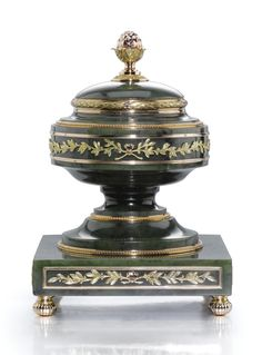 A Fabergé gold-mounted nephrite inkwell, workmaster Henrik Wigström, St Petersburg, 1903-1904, in neoclassical taste, the sides of the circular well and square plinth applied with chased two-colour gold ribbon-tied laurel sprays within reeded gold borders, the stepped base with beaded borders, the domed and hinged lid with fir cone finial above bound laurel rim mount.