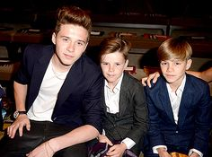 Brooklyn, Cruz and Romeo Beckham sitting front row at a fashion show.