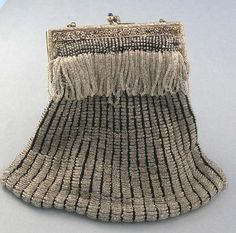 Vintage flapper purse with clear glass against black knitted background.