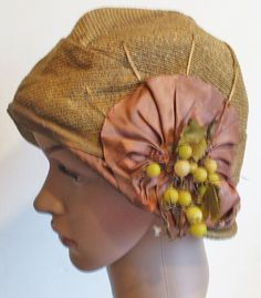 In good clean sound condition could use a steaming to freshen. Pink mauve ribbon over brim has shattered at edge. Many missing leaves and glass fruit. The interior and exterior of the hat are free of spots, loose threads, and no perspiration stains.
