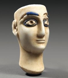 Tête provenant d'une statuette composite (Princesse de Bactriane) représentant le visage d'une femme, les yeux et les sourcils incrustés.Calcite et lapis-lazuli. Asie Occidentale,deuxieme moitie du IIIe millenaire av JC