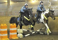How to handcuff a suspect while atop a horse: St. Paul cops are trained in mounted patrol—Two of the new St Paul Police Department mounted officers, Jennifer Mink, left, on her horse Jett, & Hank Price on Cowboy demonstrate how their horses can negotiate obstacles during a chase as city's 3 new mounted officers went through their graduation day ceremonies with demonstrations of their equestrian abilities Friday April 12, 2013 at Meadowview Stables in Woodbury. (Photo: John Doman, Pioneer…