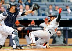 Nick Markakis #21 of the Baltimore Orioles scores a first inning run on a sacrifice fly ahead of the tag from Brian McCann