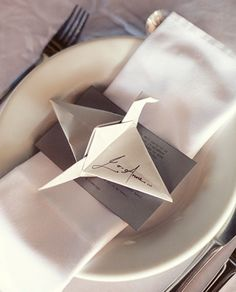 Origami on plate, for guests to sign for the bride and groom.