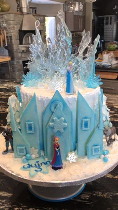 A Frozen Birthday cake for beautiful Quinn Sugar ice sugar snowflakes the Castle Anna Elsa Buttercream frosting layers of pumpkin cake chocolate cake and caramel ganache filling Elsa Birthday Cake, Frozen Themed Birthday Cake, Frozen Theme Cake, Disney Frozen Birthday, Themed Cakes, Disney Frozen Cake, Elsa And Anna Birthday Party, Frozen Dessert Table, Frozen Doll Cake