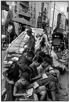 Kids devour the illustrated stories by wandering book vendors, Shanghai, 1949 by Henri Cartier-Bresson