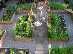 Potager, kitchen garden, raised beds, gravel paths, and an arched trellis connecting the center raised beds. from Flower Garden Girl blog.