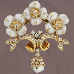Contemporary 18K Yellow gold pin featuring three Biwa pearl flowers with diamond centers atop a round cut diamond set scroll with a hanging diamond capped pearl.