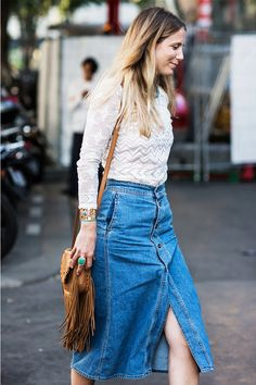 A lace top is worn with a denim skirt, a fringe bag, and turquoise jewelry