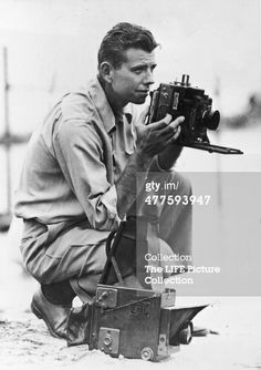 American photographer Bob Landry crouches down with his camera to line up a shot, 1945. (Photo by Bob Landry/Time & Life Pictures/Getty Images)