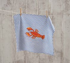 "Lobster Kitchen Towel. Blue rope links provide the nautical backdrop for our Lobster. ""Sea la vie"" phrase is written in a wrap style under his claw. Created from floursack cotton, providing a lightweight and quick drying towel for the kitchen. Also makes a cute bib for your next lobster or clam bake."