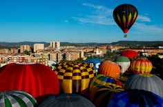 A Hot air balloons flies over Igualada during an early flight as part of the European Balloon Festival on July 10, 2014 in Igualada, Spain. The early morning flight of over 30 balloons was shorter than expected due to windy weather. This flight is organised as a curtain raiser for the four-day European Balloon Festival. Now is the 18th year of the most important hot air Balloon event in Spain and one of the biggest in Europe. (Photo by David Ramos/Getty Images)