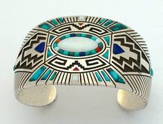 "Lee Yazzie, Navajo, ""Sunburst Bracelet,"" ca. 1985, silver overlay and mosaic inlay, opal, natural turquoise, Mediterranean red coral, lapis lazuli. EXHIBITIONS: ""Glittering World,"" 2014-2015, Smithsonian NMAI, New York, NY; COLLECTION: Gregory Schaaf and Angie Schaaf, Santa Fe; PUBLICATIONS: Gregory Schaaf and Angie Schaaf, ""American Indian Jewelry III: 2,200 Artist Biographies,"" Santa Fe, NM: CIAC Press, 2013; Lois Dubin, ""Glittering World,"" New York, NY: Smithsonian NMAI, 2014."