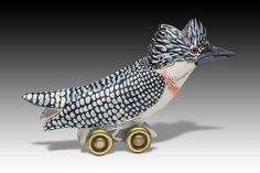 Crested Kingfisher by Dona Dalton. Whether traveling by wing or by wheel, this charming kingfisher is happy to perch anywhere in your home. Lifelike markings are meticulously painted with latex enamel on poplar wood that has been carved with a band saw. Each is unique and will vary.