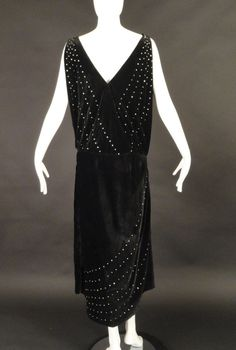1920s Black Velvet & Rhinestone Evening Gown. The bodice crosses in front with a plunging neckline in front and back. The bodice is open down the sides to the dropped waistline. Underbodice or chemise is also in velvet and creates the modesty panel across the chest and is shown at the sides where the over bodice splits. The skirt has a wrap style with the front panel open down the left side and the back. Back