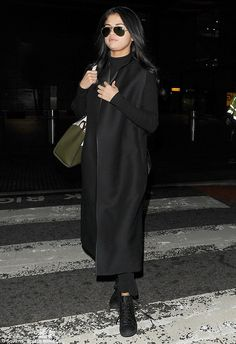 The pop starlet went for an extremely low-key look in baggy black trousers with a roll-neck jumper and a long coat Selena Gomez Outfits, Selena Gomez Style, Roll Neck Jumpers, Black Trousers, Low Key, Normcore, London, Coat, Heathrow Airport
