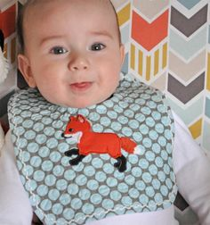 """Drool on sweet baby boy! This quilted cotton baby bib is adorned with a machine applique baby fox design from """"Baby Fox"""" design collection by A Bit of Stitch. Sashiko flip-stitched cording decorates the edge so sweetly!"""