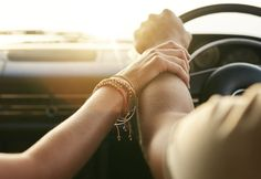 Couple traveling by car and holding hands