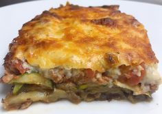 A layered oven baked casserole dish made with meat and vegetables. The most well-known version is made with layers of eggplant slices, meat sauce and cheese, topped with a thick  béchamel sauce; furthermore, other favorites call for potatoes, zucchini, or a combination of vegetables (this one includes the sliced potatoes and zucchini). It's worth every minute.  #casserole #eggplant #babymarrow #zucchini #greek #moussaka #greekfood #potatoes #spicedmeat #greekmoussaka Greek Recipes, New Recipes, Vegan Recipes, Whole Roasted Cauliflower, Peanut Butter Smoothie, Moussaka, Sliced Potatoes, Meat Sauce, Latest Recipe