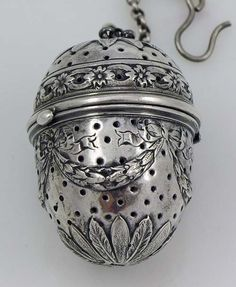 """German Sterling Ornate Tea Ball    A sterling silver large ornate tea ball with hand chased decoration of swags and leaves. The top hinges to open and has the original chain and hook. Marked sterling with German pseudo marks. Length 2""""; weight 1.65 troy ounces.    Price: 375.00"""
