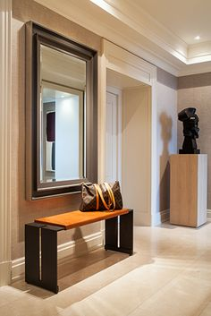 Stylish entryway. The huge mirror, the pop up of orange colour and the artwork make this space so special yet sophisticated