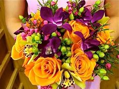 A mock up of a bridal bouquet with orange roses, hypericum berries, purple dendrobiums, green cymbidiums and beronia heather.