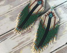 Magical & earthy, Native American inspired seed bead fringe earrings. Traditionally Native American women adorned themselves with seed bead earrings for their weddings. Length: 5 inches Width: 1.5 inches Light weight, easy to wear, prefect for any occasion. Effortless beauty, earthy, fit for a queen, celestial goddess, shaman, witch, alien, being of light, faerie, whoever, whatever. Reconnect with your inner nature spirit when you adorn your crown with these sweeping beauties. ***each p...