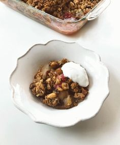 Baked pear and rhubarb crisp in a white bowl with a dollop of Greek yogurt